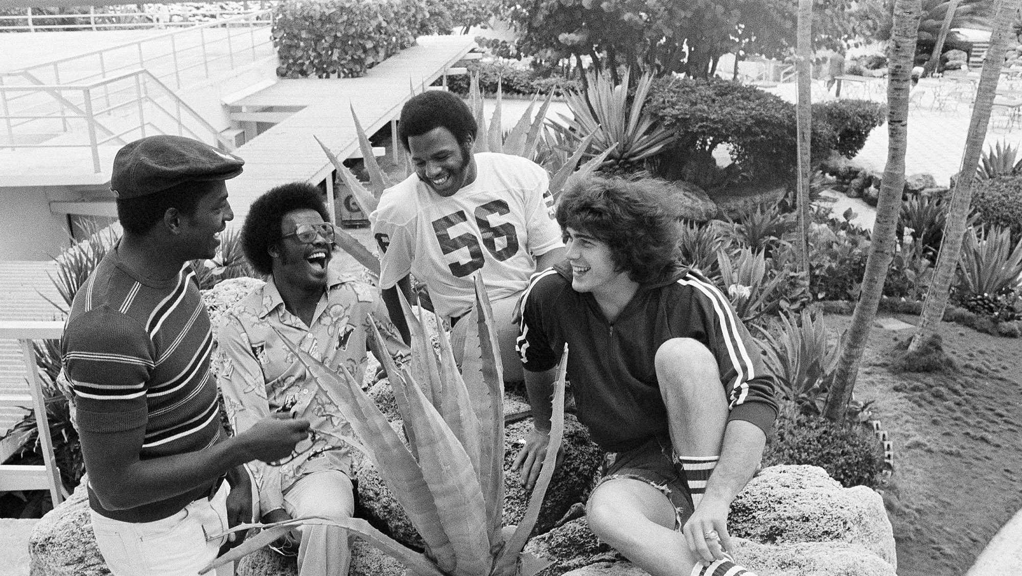 "Members of the Oklahoma Sooners relax around the gardens of their hotel on Miami Beach, Fla., Dec. 29, 1975. From left: ""Wild Man"" Victor Brown, Mike Phillips, Glenn Comeaux and ""Tarman"" Jimbo Elrod. (AP Photo/Bill Hudson)"