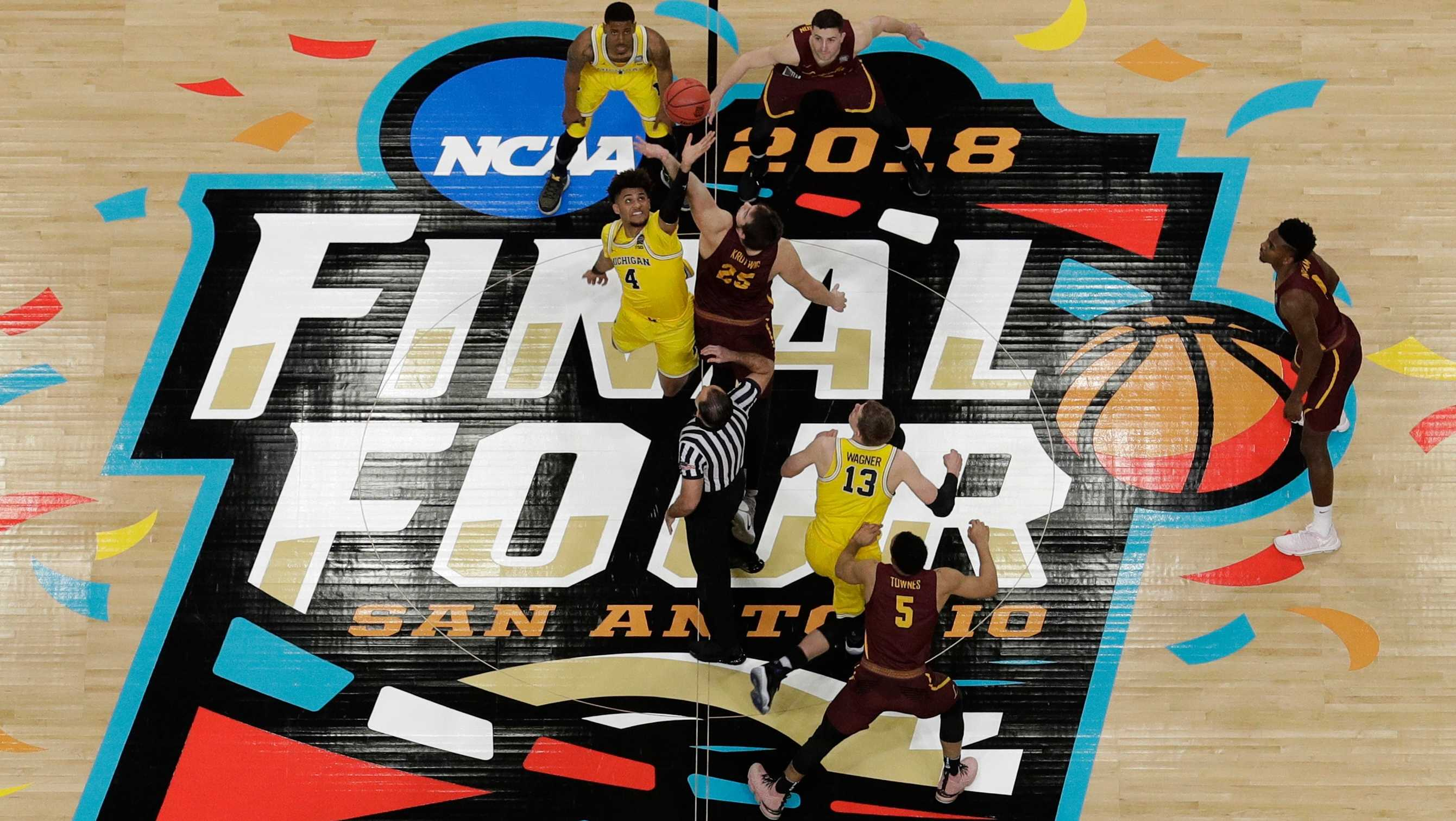 Michigan's Isaiah Livers (4) and Loyola-Chicago's Cameron Krutwig (25) battle for the ball at the tip off during the first half in the semifinals of the Final Four NCAA college basketball tournament, Saturday, March 31, 2018, in San Antonio.