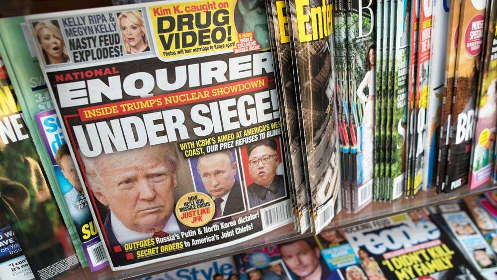In this Wednesday, July 12, 2017 photo, an issue of the National Enquirer featuring President Donald Trump on it's cover is seen at a store in New York.