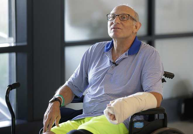 William Lytton, of Scarsdale, N.Y., is seated in a wheelchair while taking a break from physical therapy at Spaulding Rehabilitation Hospital, in Boston, Tuesday, Aug. 28, 2018, while recovering from a shark attack. Lytton suffered deep puncture wounds to his leg and torso after being attacked by a shark on Aug. 15, 2018 while swimming off a beach, in Truro, Mass. Lytton injured a tendon in his arm while fighting off the shark. (AP Photo/Steven Senne)