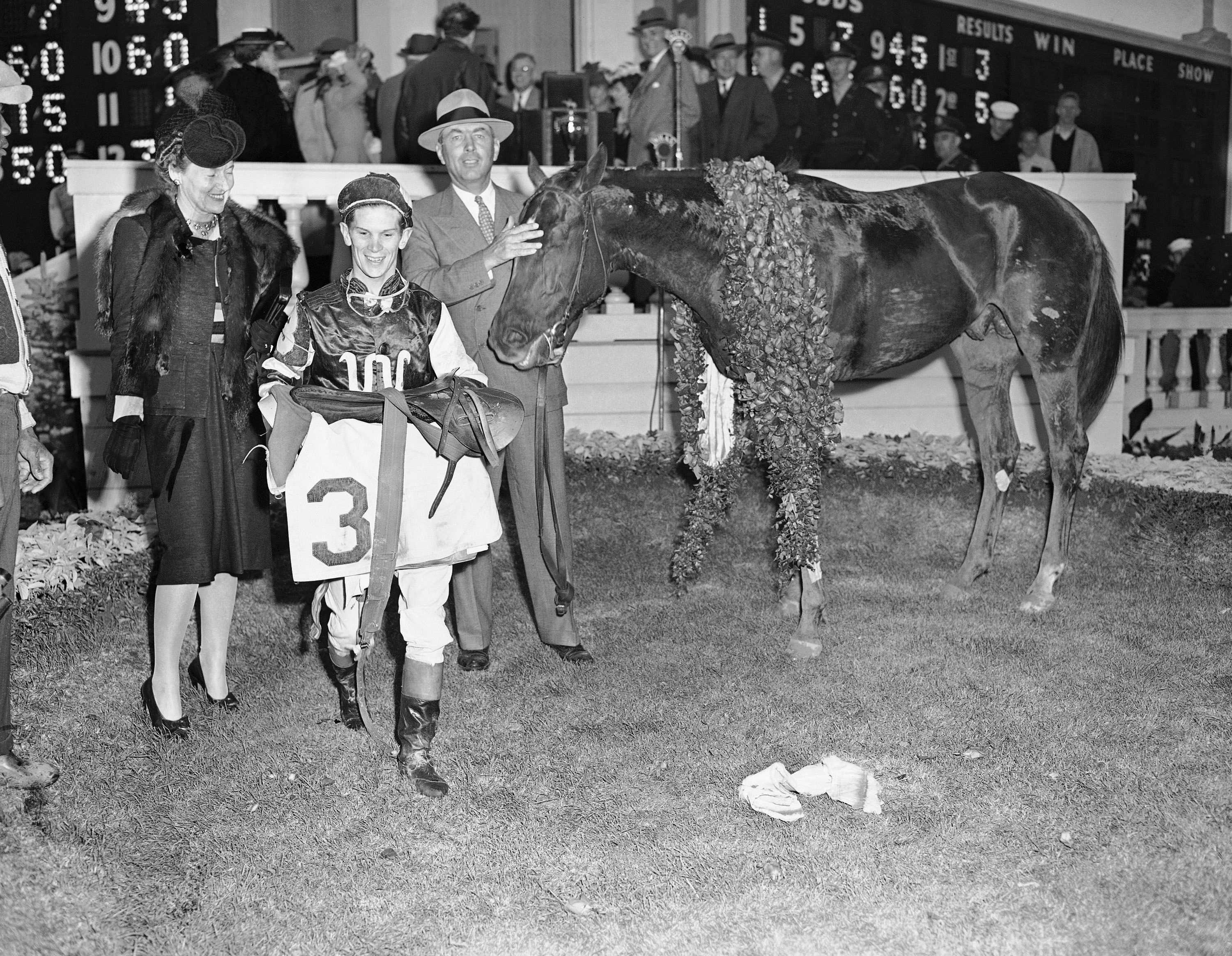 Wearing a garland of Roses, Assault stands in the Kentucky Derby winner's circle, May 4, 1946 at Louisville, with (left to right) Mrs. Robert J. Kleberg, Jr.&#x3B; Jockey Warren Mehrtens&#x3B; and owner Robert J. Kleberg, Jr. of King Ranch, Texas.