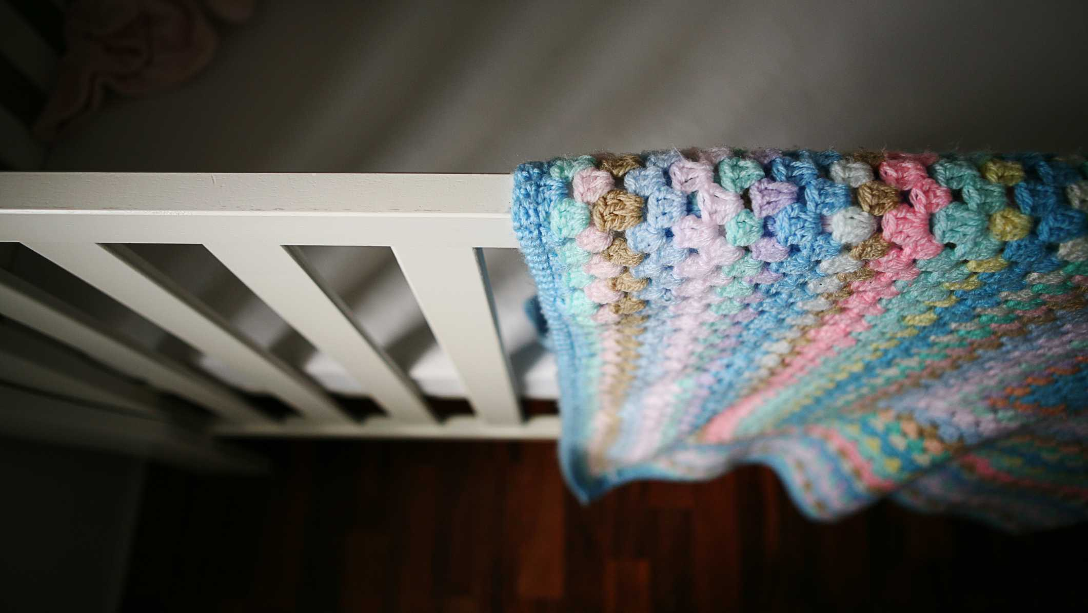 Empty baby's cot with shadows and crocheted blanket.