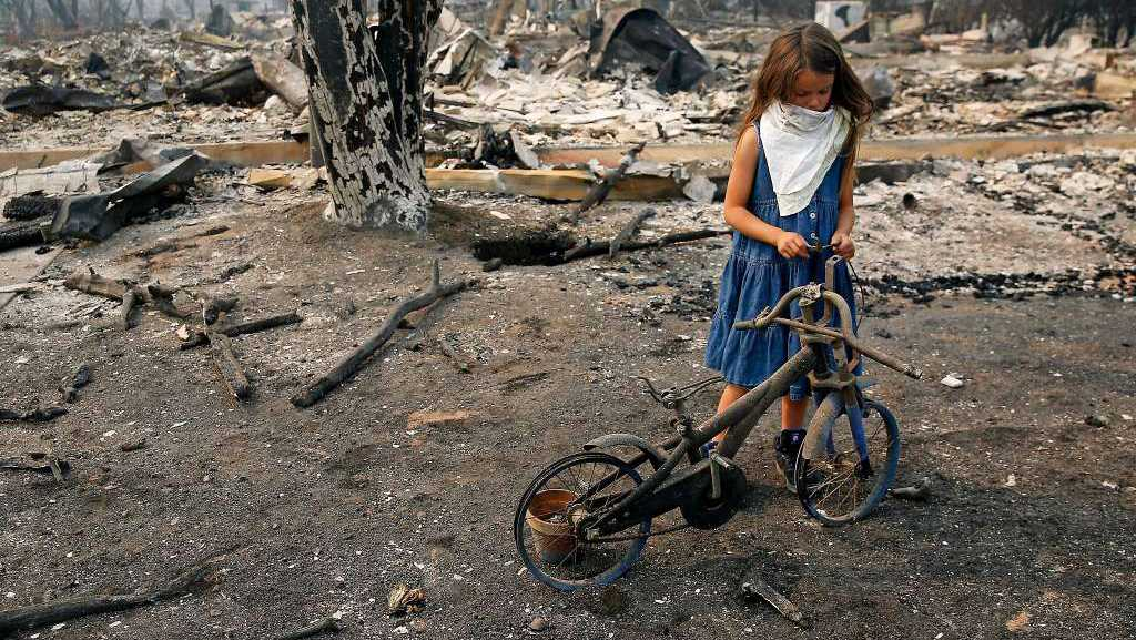 Arilyn Edwards, 6, stands beside her bike in front of the rubble of her Santa Rosa home.