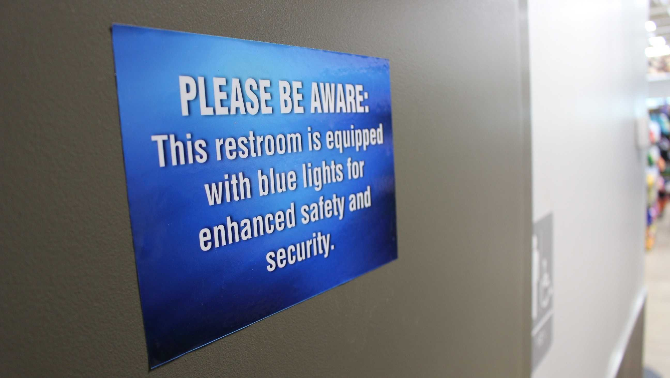 In this June 22, 2018 photo, a sign outside a public bathroom hangs at this Turkey Hill convenience store in Wilkes-Barre, Pa. The chain has installed blue light bulbs in some of its stores in hopes of discouraging drug use by making it harder for people to see their veins.