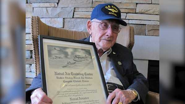 In this Wednesday, April 25, 2018 photo, World War II veteran Bob Barger poses with his Naval flight school certificate in Toledo, Ohio. Barger is set to graduate from the University of Toledo after a review of his transcripts showed he completed enough classes in the late 1940s for a two-year degree.
