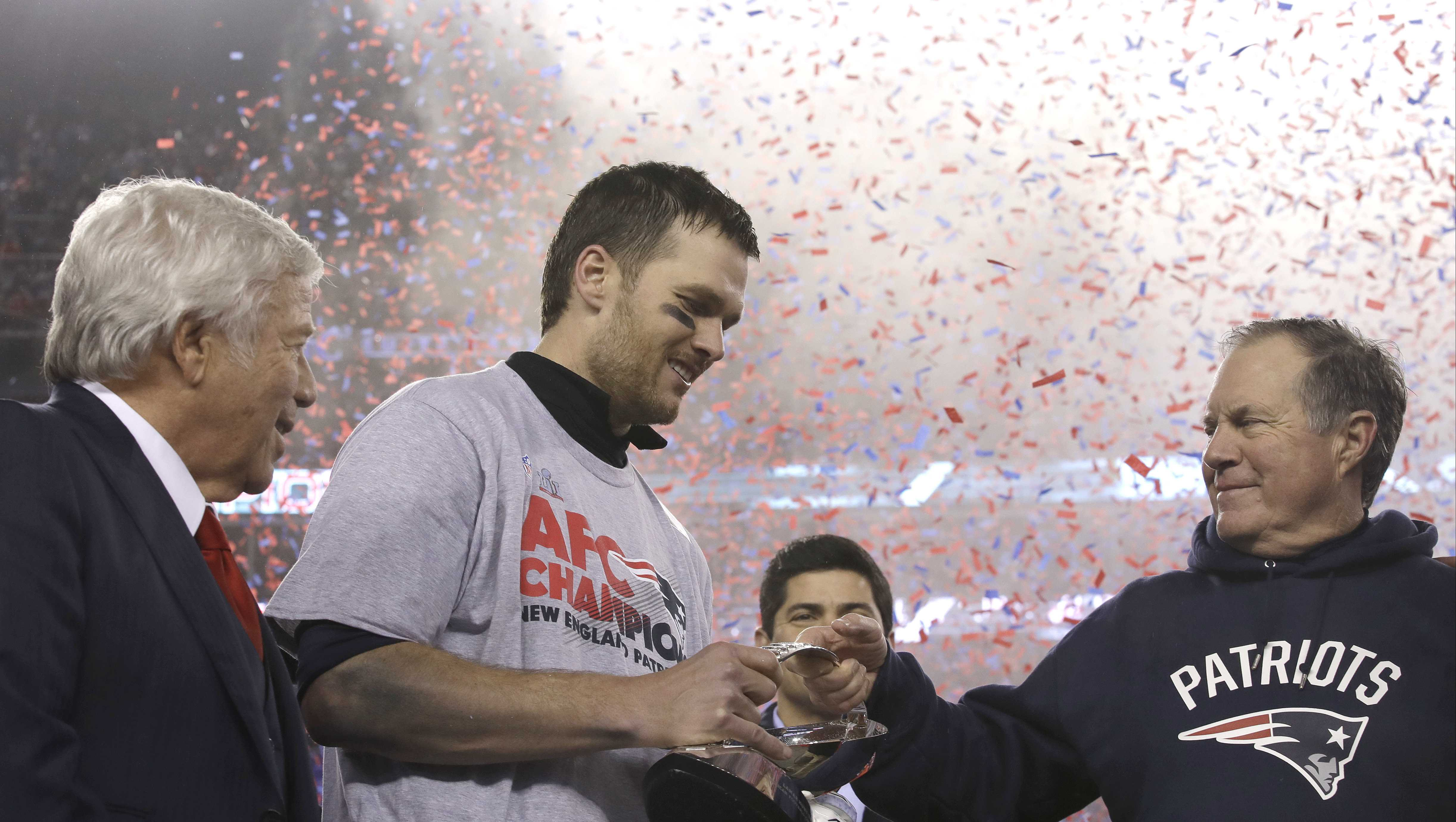 New England Patriots head coach Bill Belichick, right, passes the AFC Championship trophy to quarterback Tom Brady after winning the AFC championship NFL football game against the Pittsburgh Steelers, Sunday, Jan. 22, 2017, in Foxborough, Mass. At left is team owner Robert Kraft. The Patriots defeated the the Steelers 36-17 to advance to the Super Bowl.