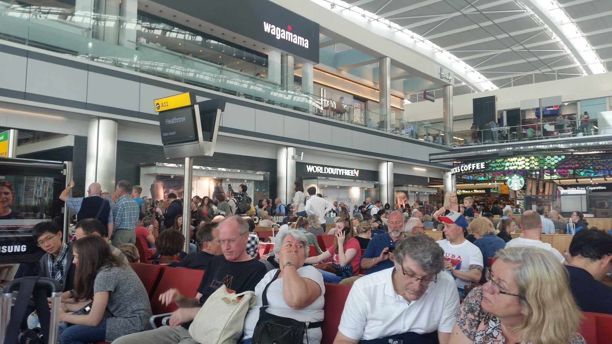 The waiting area at Heathrow airport as passengers are waiting for details about flights.