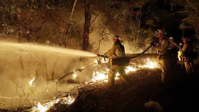 Fire crews battle a wildfire Saturday, Oct. 14, 2017, in Santa Rosa, Calif.