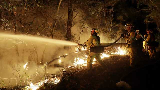 Fire crews battle a wildfire Saturday, Oct. 14, 2017, in Santa Rosa, Calif.