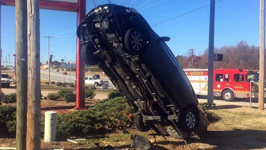 A car in Greer, SC hangs on wires.