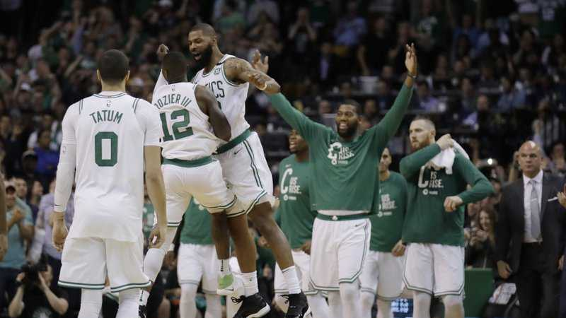 Boston Celtics guard Terry Rozier (12) and forward Marcus Morris leap in celebration near the end of Game 2 of the team's NBA basketball Eastern Conference finals against the Cleveland Cavaliers, Tuesday, May 15, 2018, in Boston.