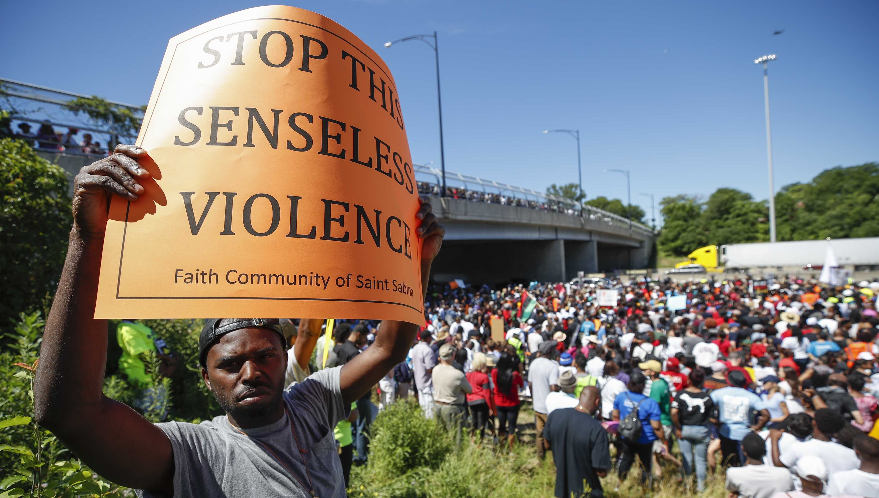 An activist holds a sign during march along Chicago Dan Ryan Expressway to protest violence in the city on July 7, 2018 in Chicago, Illinois.
