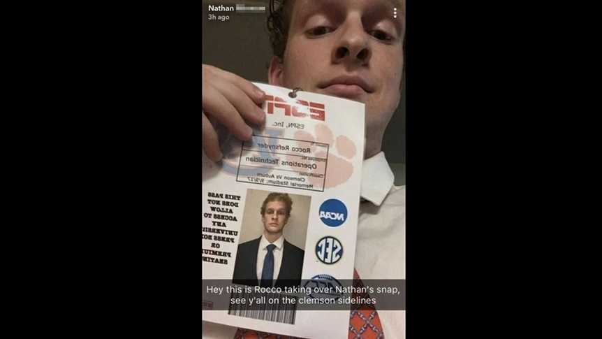 A Clemson University student holds up the ESPN ID badge he faked to get on the sidelines of a recent game.