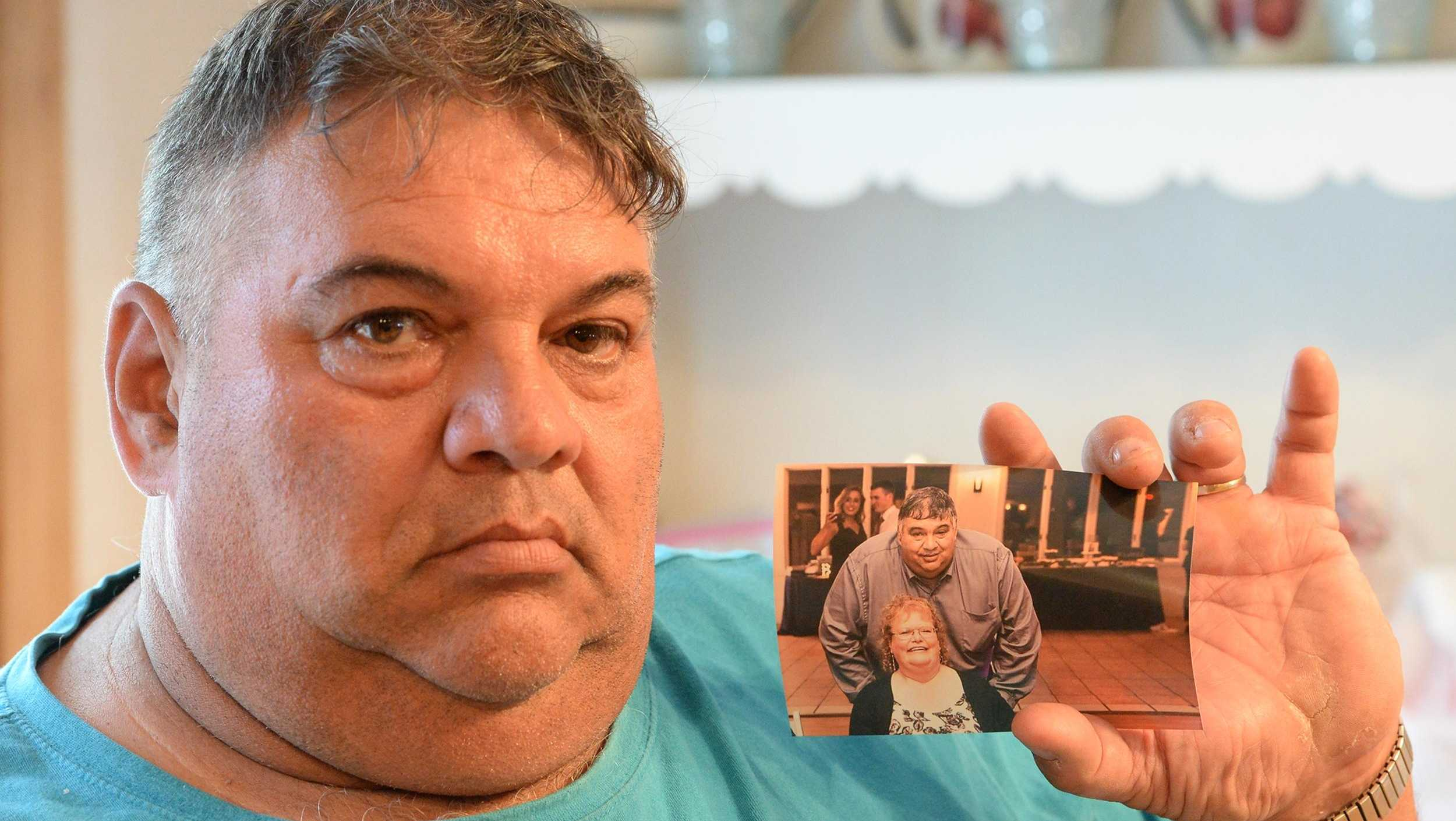 Manuel 'Manny' Combra holds a photograph of his late wife Deborah.