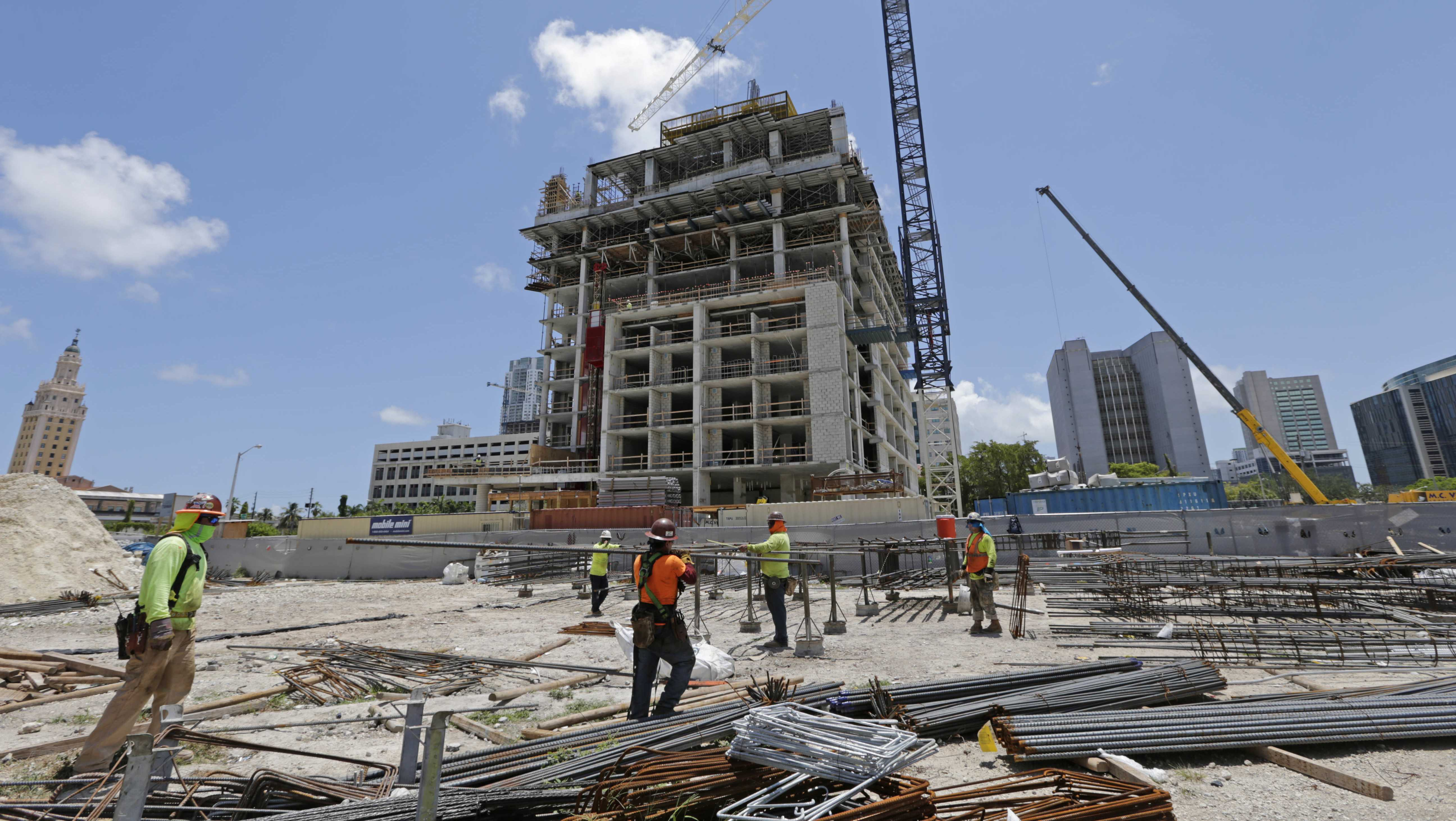 In this Thursday, May 4, 2017, photo, construction workers work on site of an apartment high rise in Miami.