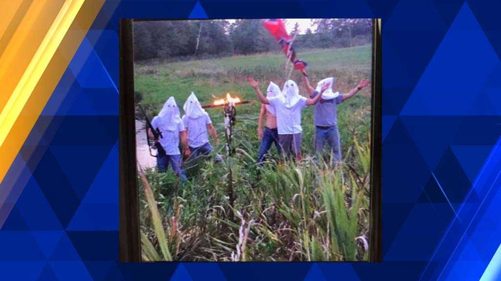 Photo surfaces showing students in white hoods with burning cross