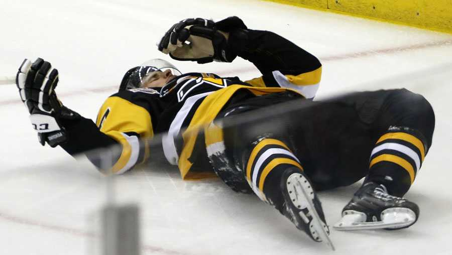Sidney Crosby lies on the ice after taking a hit from Matt Niskanen.