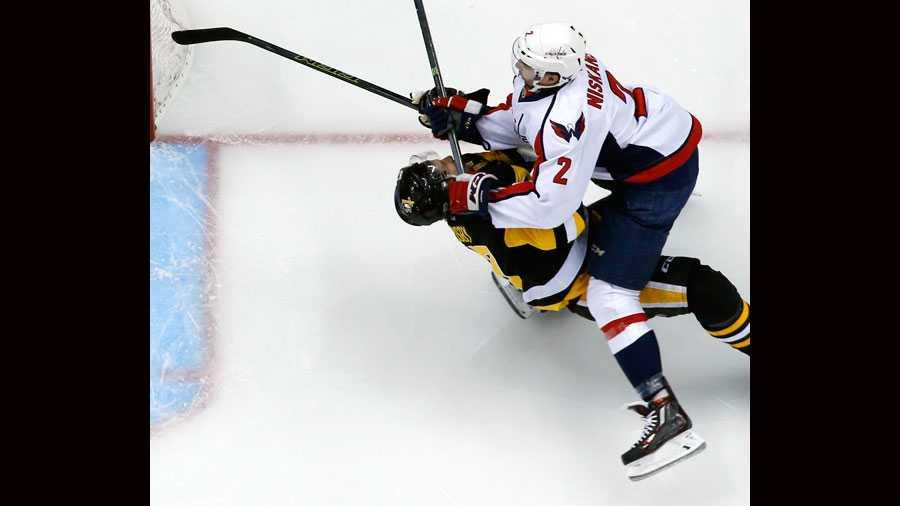 Sidney Crosby takes a hit from Matt Niskanen.
