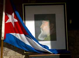 An image of Fidel Castro and a Cuban flag are displayed in honor of the late leader one day after he died, inside the foreign ministry in Havana, Cuba, Saturday, Nov. 26, 2016. Castro, who led a rebel army to improbable victory, embraced Soviet-style communism and defied the power of 10 U.S. presidents during his half century rule of Cuba, died at age 90 late Friday.