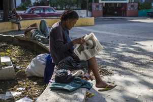 Former teacher Adis Tamayo reads the Juventud Rebelde newspaper with the latest news on the death of Cuban leader Fidel Castro, on a street in Havana.