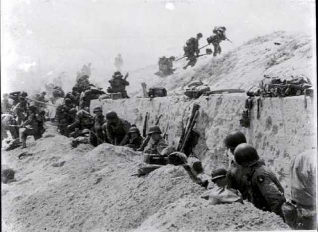 Soldiers of the 8th Infantry Regiment, 4th Infantry Division, move over a seawall on Utah Beach during the Allied Invasion of Europe.