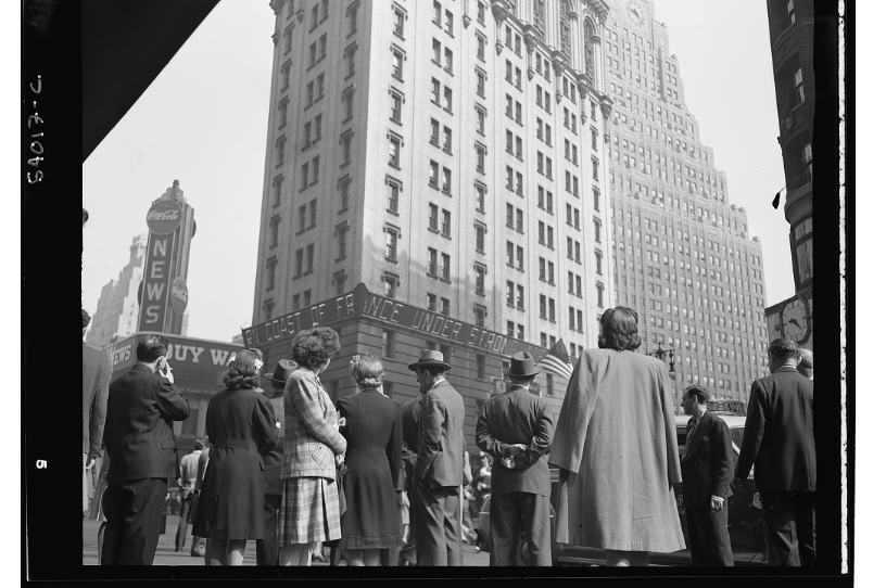 A crowd in New York City watches a news ticker giving information on the D-Day landings in Normandy.
