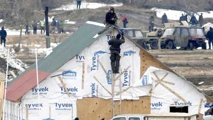 A law enforcement officer climbs a ladder to speak to one of the final holdouts of the Dakota Access Pipeline protest camp sitting atop a wood structure built at the Oceti Sakowin camp in Morton County Thursday, Feb. 23, 2017, near Cannon Ball, N.D. After a couple of hours the protester came down on his own and was arrested.