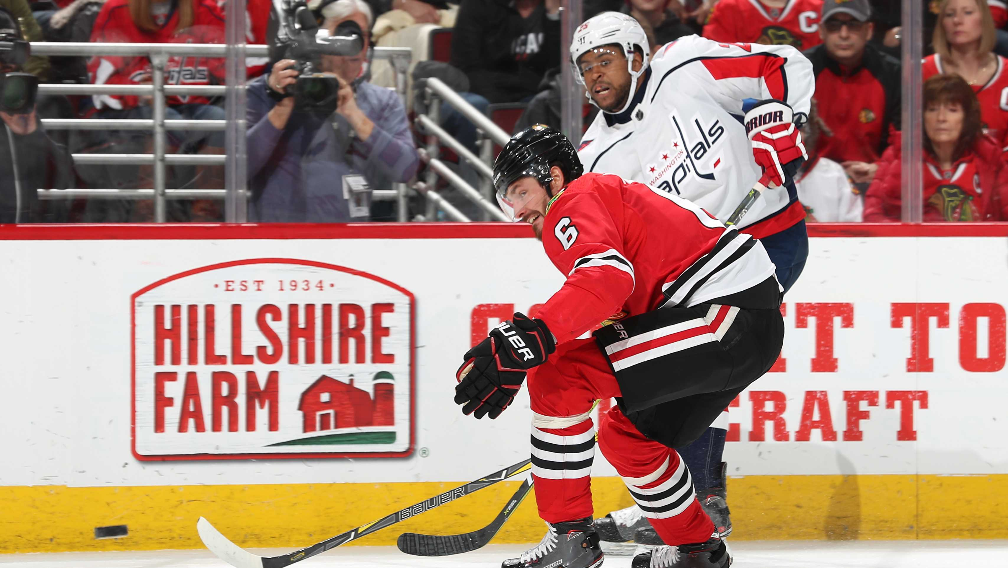 Michal Kempny #6 of the Chicago Blackhawks and Devante Smith-Pelly #25 of the Washington Capitals watch the puck in the first period at the United Center on February 17, 2018 in Chicago, Illinois.