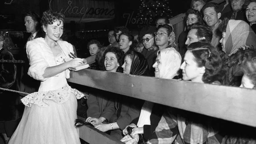 Debbie Reynolds signs autographs at a 1949 movie premiere for 'The Hasty Heart.'