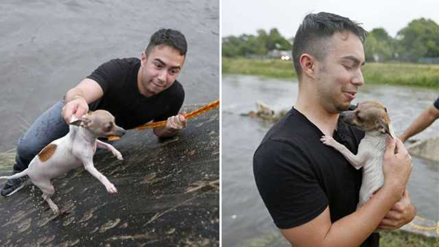 San Antonio Express-News reporter Alexandro Luna holds a dog he rescued from the drainage ditch at Woodlawn Lake Park with the help of Park Police Officer David Ramirez (rear) Sunday May 20, 2018.