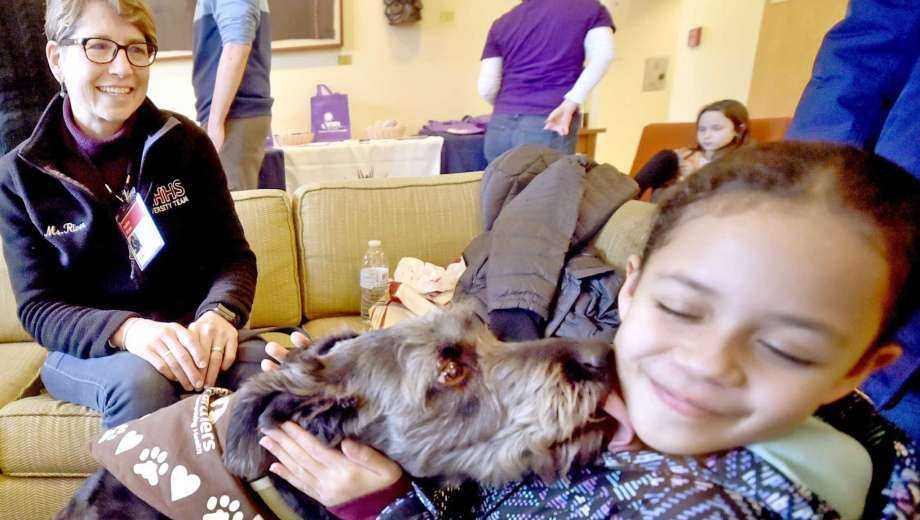Leila Martinez, 8, of New Haven, right, gets a kiss from certified therapy dog Sophia, a rescued mixed-breed, on Saturday with her handler Roben River, of Woodbridge, representing dog training facility Paw's N' Effect of Hamden.