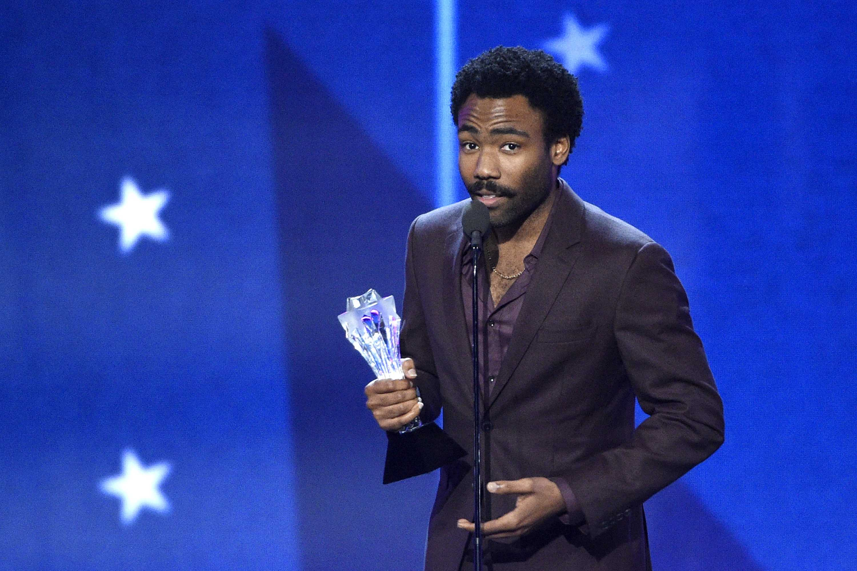 "Donald Glover accepts the award for best actor in a comedy series for ""Atlanta"" at the 22nd annual Critics' Choice Awards at the Barker Hangar on Sunday, Dec. 11, 2016, in Santa Monica, Calif."