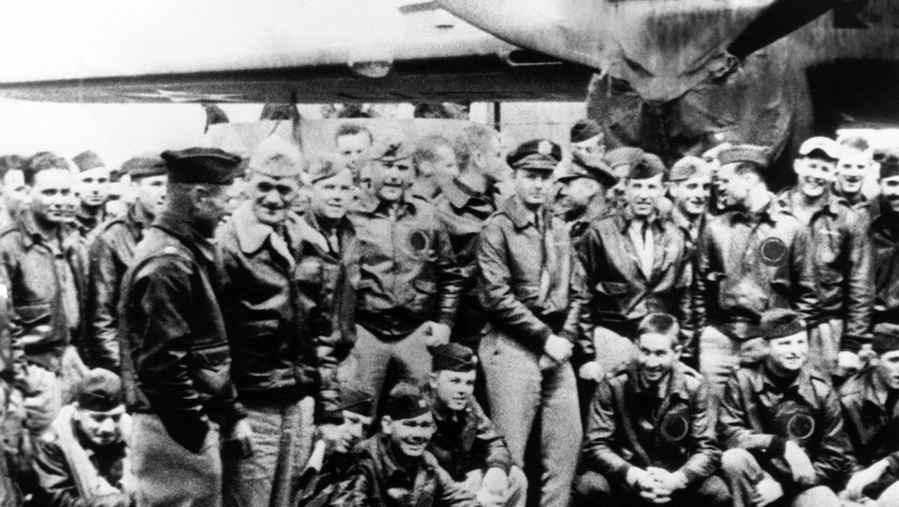 Orders in his hand, Capt. Marc A. Mitscher, skipper of the U.S.S. Hornet, discusses details for the take-off of Army members for the Tokyo raid with Maj. Gen. James H. Doolittle (left in left foreground). Many of the 80 pilots who made the raid, April 18, 1942, stand or squat on the carrier's flight deck.