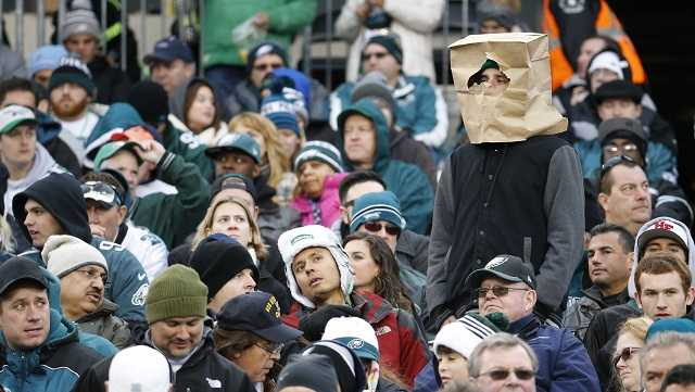 """In this Nov. 22, 2015, file photo, a fan wears a paper bag on his head in the stands of Lincoln Financial Field during the second half of an NFL football game between the Philadelphia Eagles and the Tampa Bay Buccaneers in Philadelphia. The obituary for an Eagles fan who died Aug. 18, 2017, stated that he wanted 8 members of the team to serve as pallbearers so the Eagles could let him down """"one last time."""""""