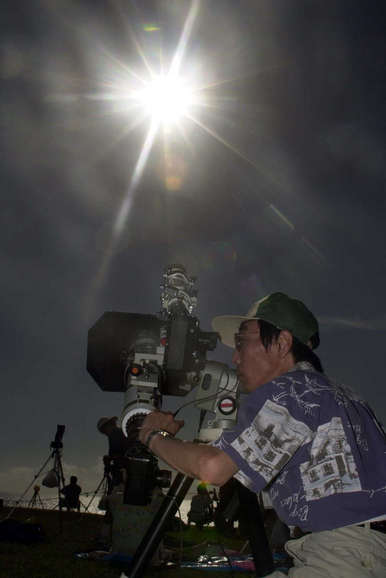 Hideo Fukushima, a staff of Japan' s National Astronomical Observatory, gazes through his camera to observe the sun during an annular eclipse at the Suicide Cliff in Tinian in the Northern Marianas Islands on the morning of June 11, 2002.