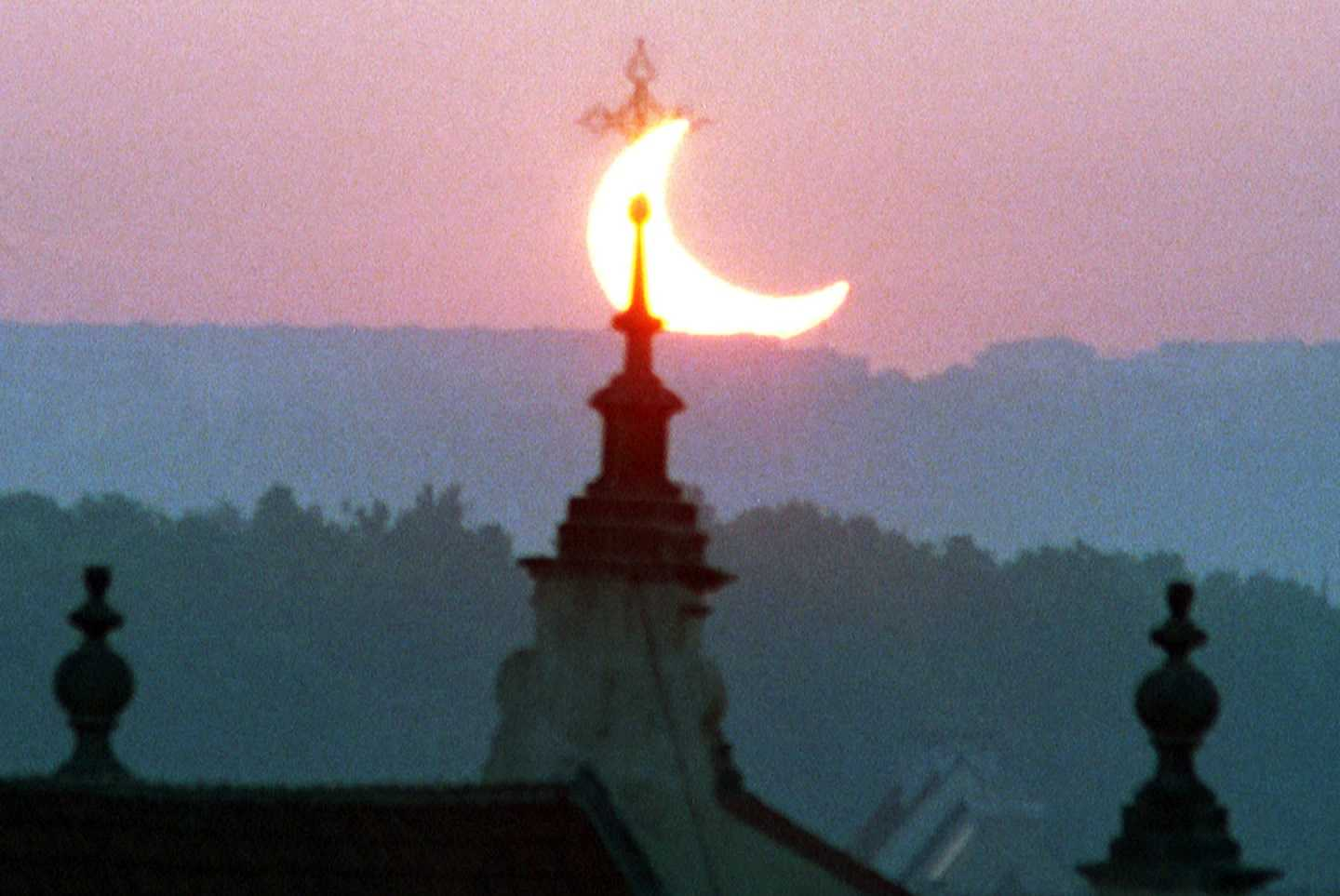 The sun is seen behind a tower of a Prague's church during a partial solar eclipse at dawn on Saturday, May 31, 2003.