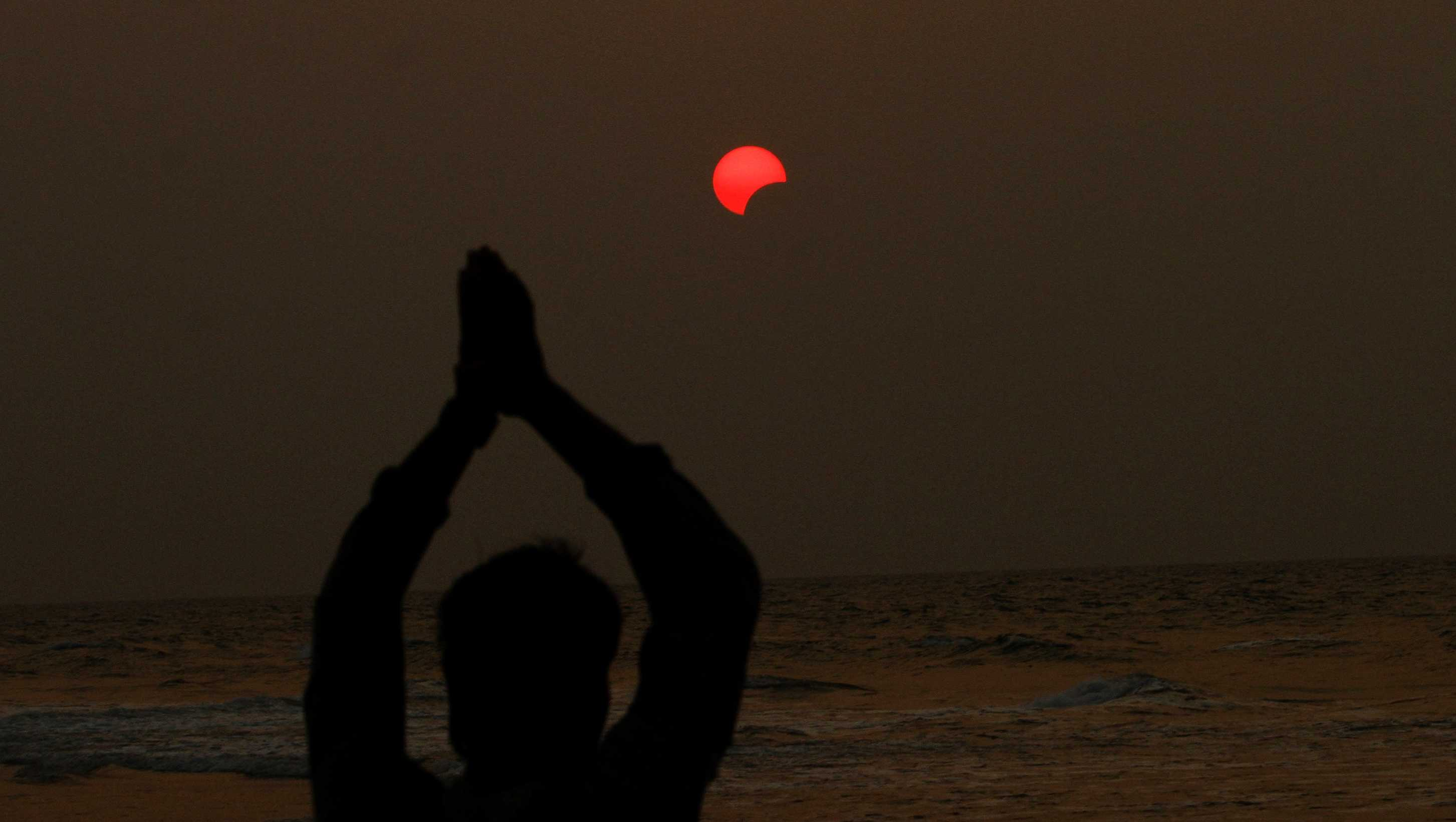 A fisherman prays during a partial solar eclipse in the sky over Bay of Bengal in Konark, 37 miles from the eastern Indian city Bhubaneswar, on Wednesday, March 9, 2016.