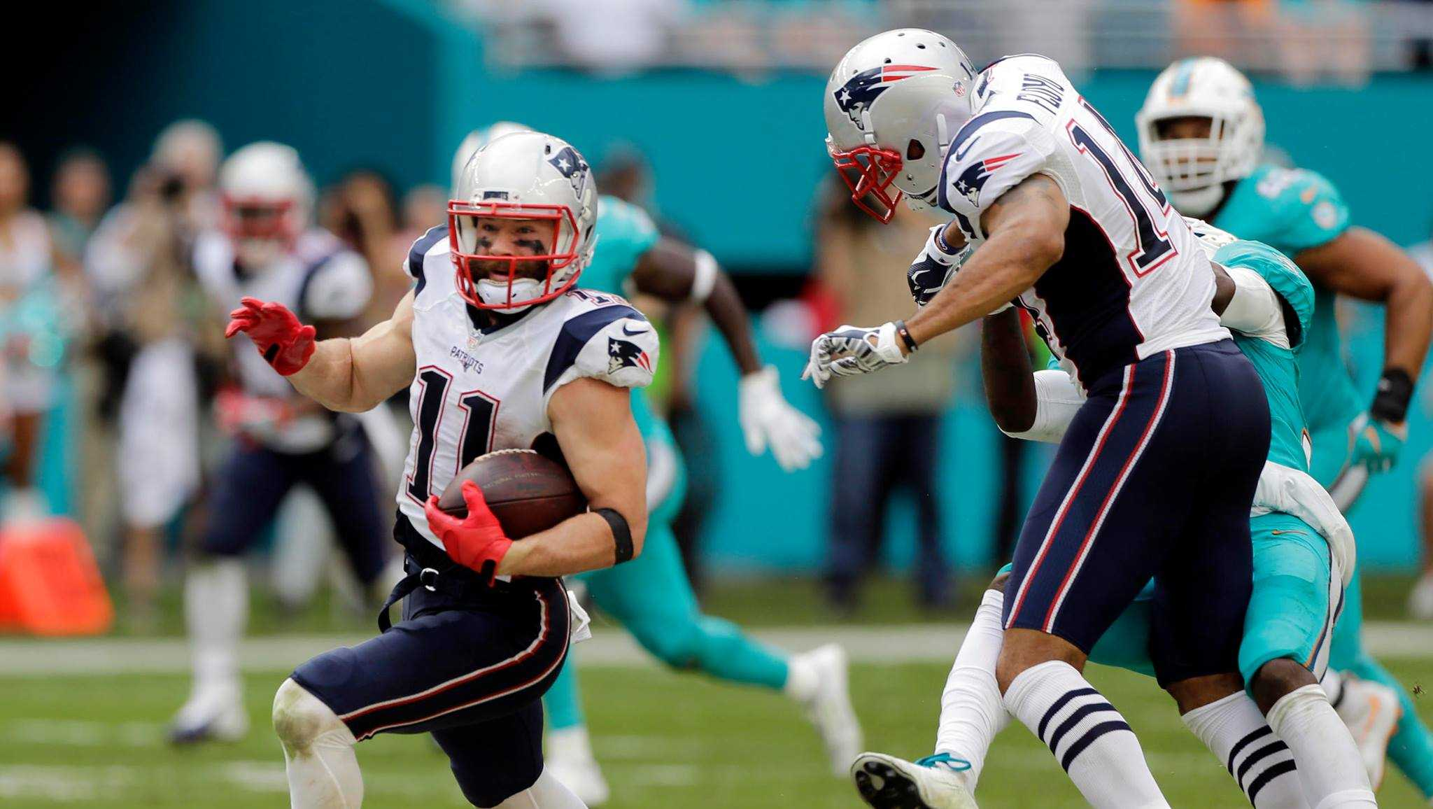 New England Patriots wide receiver Julian Edelman (11) runs for a touchdown as wide receiver Michael Floyd (14) bumps Miami Dolphins cornerback Tony Lippett (36) out of the way, during the second half of an NFL football game, Sunday, Jan. 1, 2017, in Miami Gardens, Fla.