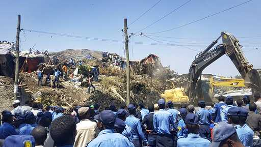 Police officers secure the perimeter at the scene of a garbage landslide, as excavators aid rescue efforts, on the outskirts of the capital Addis Ababa, Ethiopia Sunday, March 12, 2017. Officials and residents say more than a dozen people have been killed in a landslide at a massive garbage dump on the outskirts of Ethiopia's capital, and several dozen people are missing.
