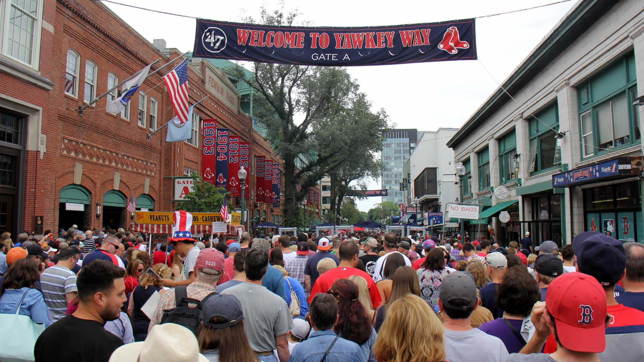 Fans line up along Yawkey Way to pass through security and enter Fenway Park.