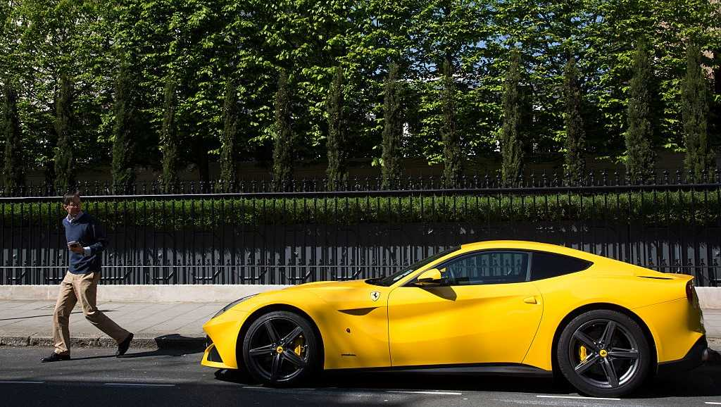 Yellow Ferrari supercar parked in front of a well kept hedge in Chapel Street in Belgravia, one of the most exclusive areas in central London