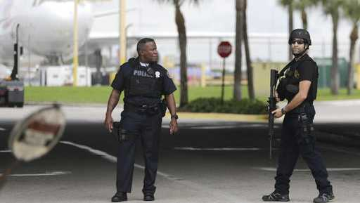 Police officers stand on the perimeter road along the Fort Lauderdale-Hollywood International Airport after a shooter opened fire inside a terminal of the airport, killing several people and wounding others being taken into custody, Friday, Jan. 6, 2017, in Fort Lauderdale, Fla