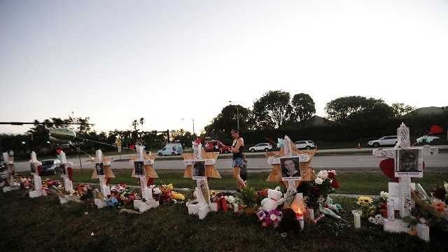 A passer-by stops at a makeshift memorial outside the Marjory Stoneman Douglas High School in Parkland, Fla., Monday, Feb. 19, 2018.