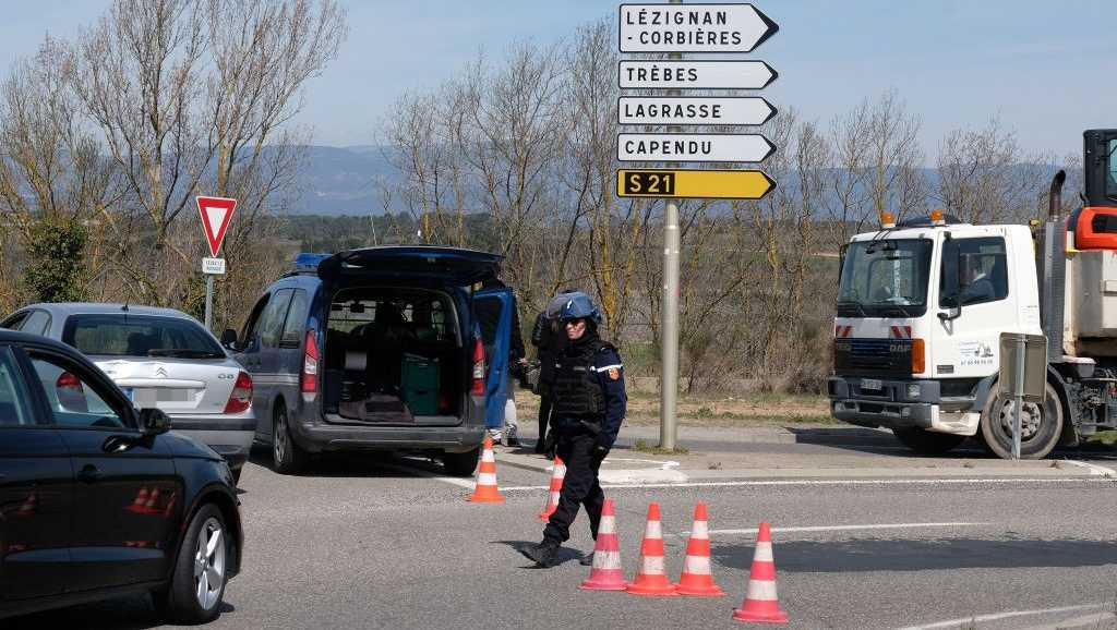 French gendarmes block the access to Trebes, where a man took hostages at a supermarket on March 23, 2018 in Trebes, southwest France.