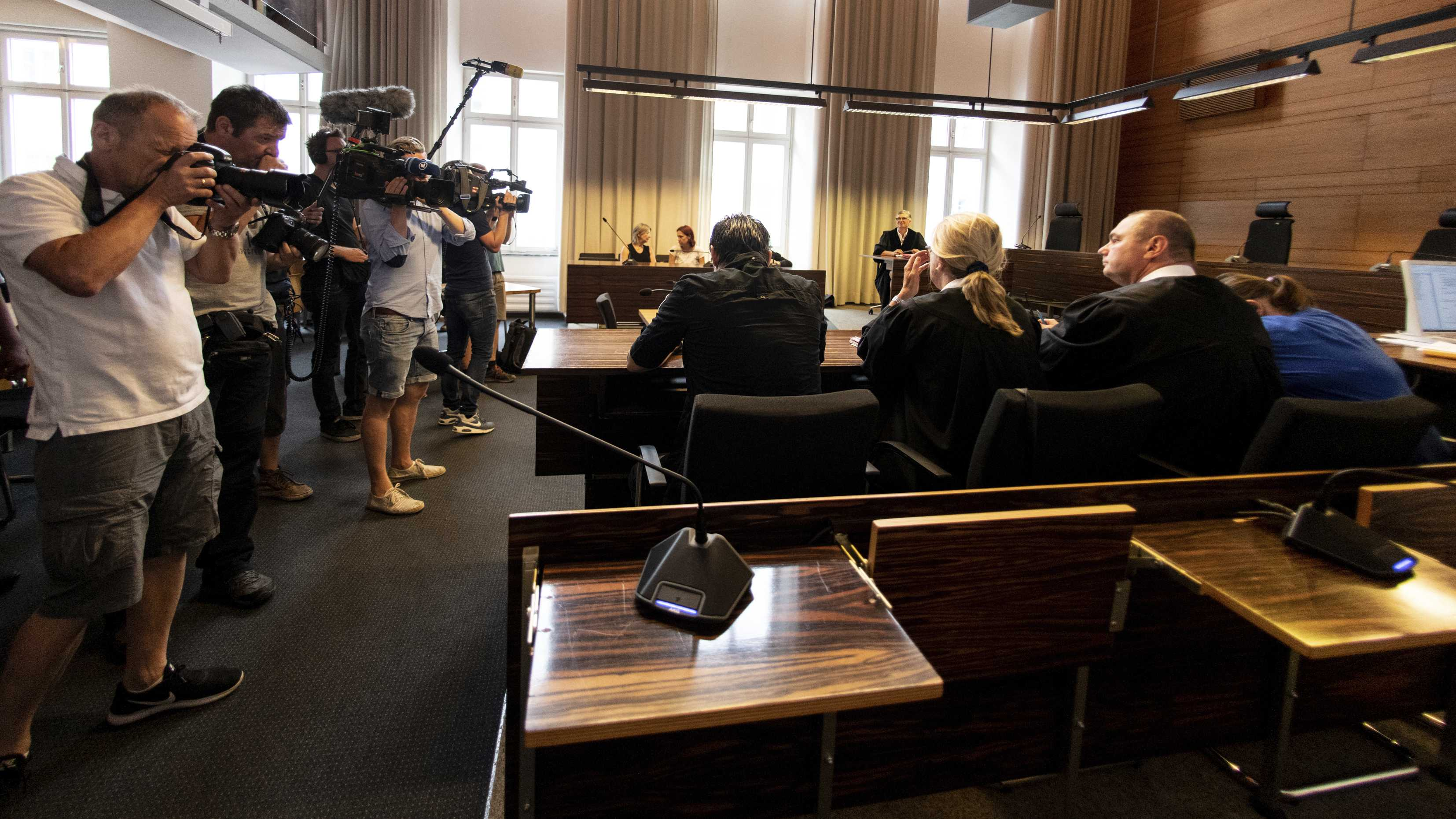 Photographers take pictures of the a man and a woman in the court in Freiburg, southern Germany, Tuesday, Aug. 7, 2018 before they were sentenced to long-term prison sentence for for offering the 9-year-old son of the woman for raping by pedophiles. (Patrick Seeger/dpa via AP)