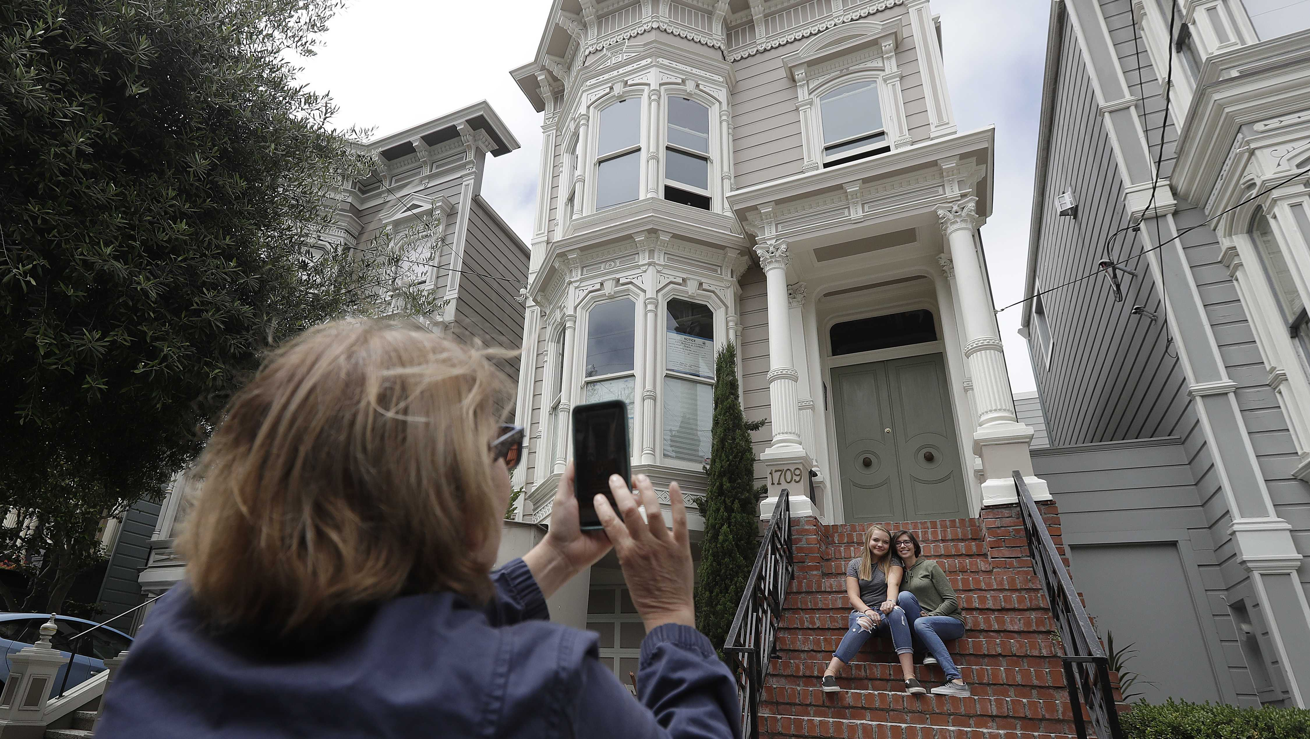 """Aries Layton, seated left, and her aunt Kelsy Layton pose as Debra Layton, Aries' grandmother and Kelsy's mother, foreground, takes photos outside a Victorian home made famous by the television show """"Full House"""" in San Francisco, Tuesday, July 17, 2018."""