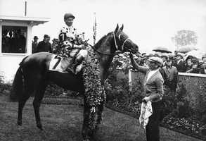 Gallant Fox, with jockey Earl Sande up, wears the roses after winning the 1930 Kentucky Derby. Gallant Fox went on to win the Triple Crown.