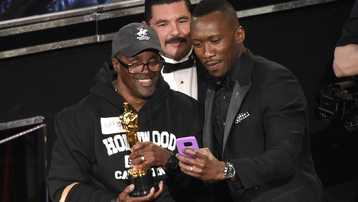 Mahershala Ali, right, takes a selfie with a tourist named Gary while holding his award for best actor in a supporting role for Moonlight at the Oscars on Sunday, Feb. 26, 2017, at the Dolby Theatre in Los Angeles.