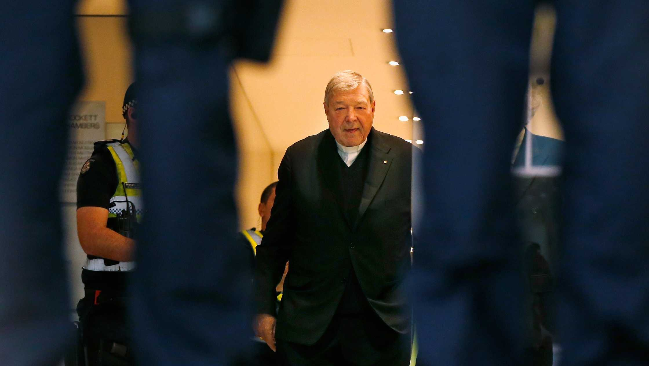 Cardinal George Pell walks with a police escort from his lawyers office to the Melbourne Magistrates' Court on October 6, 2017 in Melbourne, Australia.