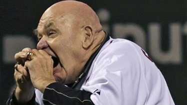 "Former professional wrestler George ""The Animal"" Steele bites the baseball before throwing out the ceremonial first pitch prior to a baseball game against the Baltimore Orioles at Fenway Park in Boston, Friday, Sept. 21, 2012."